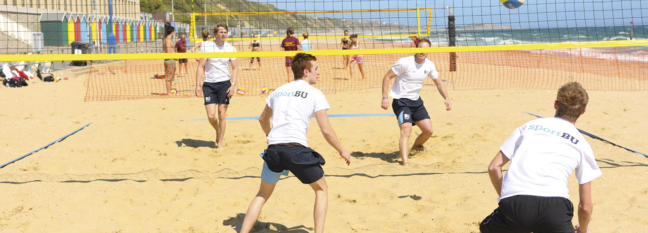 Students play beach volleyball